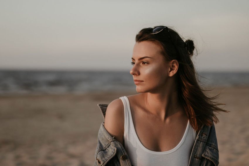 Sitting Beach Beautiful Woman Casual Clothing Contemplation Focus On Foreground Front View Hair Hairstyle Headshot Horizon Horizon Over Water Land Leisure Activity Looking Nature One Person Outdoors Portrait Sea Sky Standing Water Young Adult