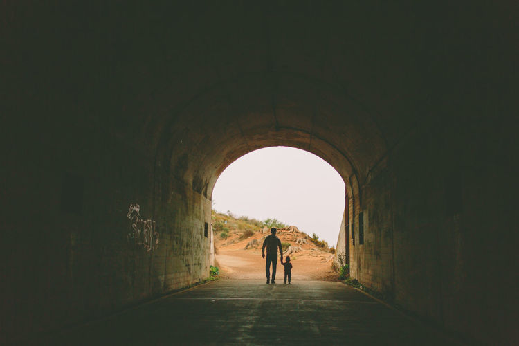 A father and son in silhouette, walking through a tunnel. Family Arch Architecture Bonding Built Structure Day Father Full Length Indoors  Leisure Activity Lifestyles Mammal Men Nature People Real People Rear View Son The Way Forward Togetherness Tunnel Two People Under Walking