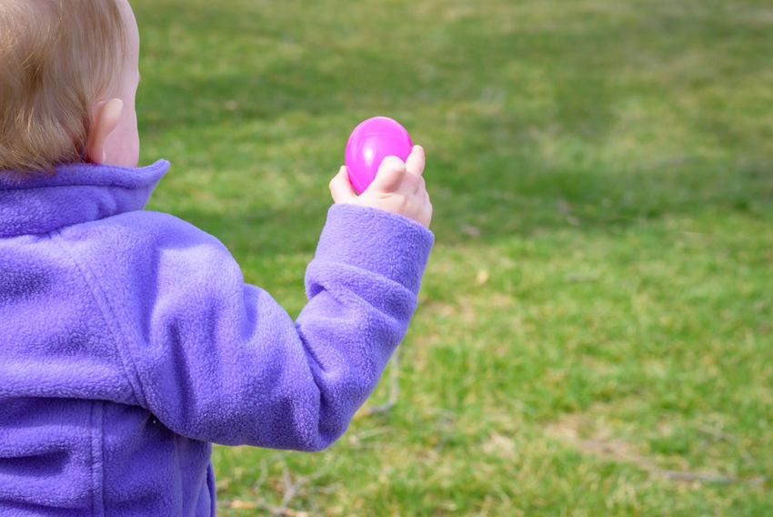 little kids having fun at Easter egg hunt outside Easter Easter Egg Hunt Holding Hands Blue Child Childhood Clothing Day Excitement Field Focus On Foreground Girls Grass Hair Hairstyle Holding Innocence Nature Offspring One Person Plant Plastic Easter Eggs Purple Rear View Women