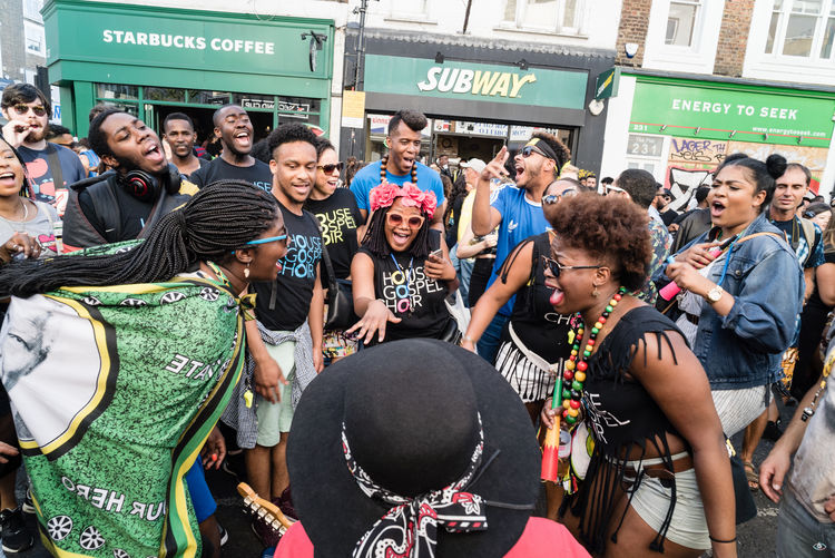 Notting Hill Carnival 2016 Building Exterior Casual Clothing Day Friendship Large Group Of People Leisure Activity Lifestyles Looking At Camera Mode Of Transport Outdoors Person Relaxation Standing Text Togetherness Transportation