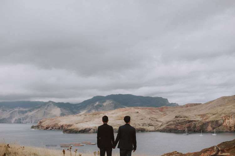 Rear view of men standing on mountain against sky