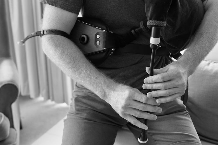 Midsection Of Man Holding Bagpipe