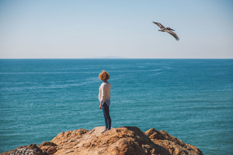 Young woman standing on rock against sea
