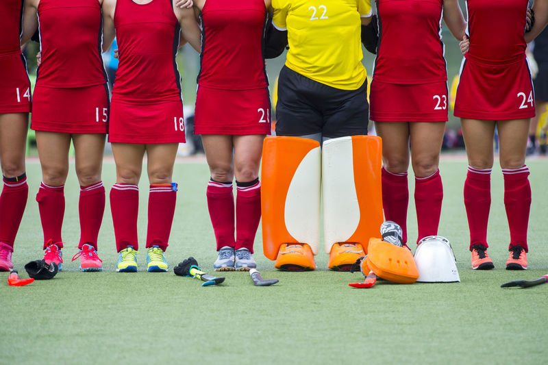 Low Section Of Female Sports Players Standing On Playing Field