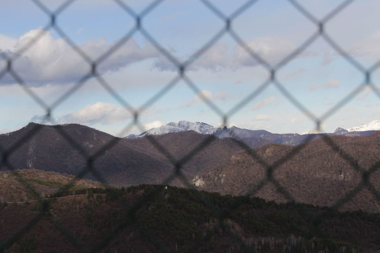 Scenic View Of Mountains Against Sky Seen From Chainlink Fence