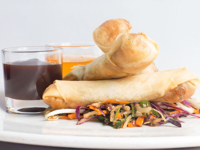 Close-up of spring rolls served with drinks in plate