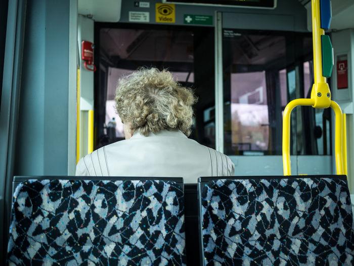 Rear View Of Senior Woman Sitting On Tram In Berlin