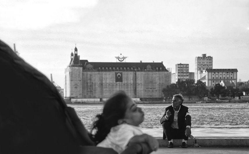 People sitting by buildings in city against sky