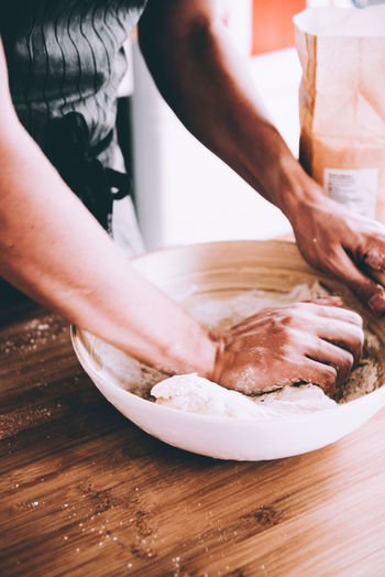 Midsection Of Man Kneading Dough In Bowl At Table