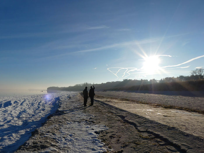 People standing at beach during winter