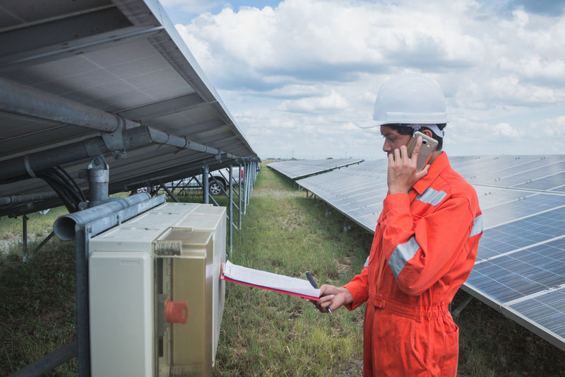 Side view of worker talking on phone while standing by solar panel