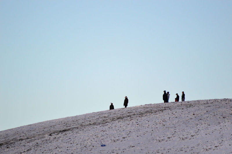 People on mountain against clear sky