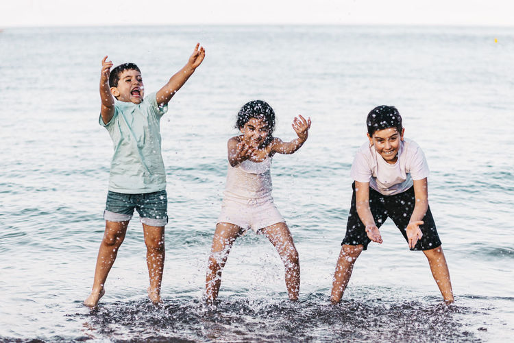 Full length of friends enjoying at beach