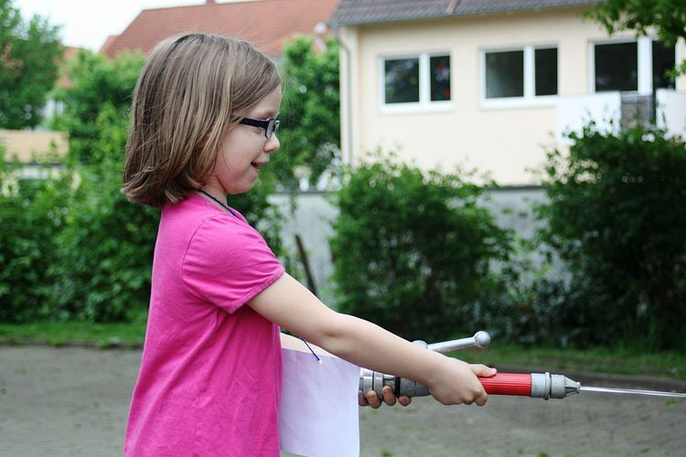 Side view of girl holding fire hose