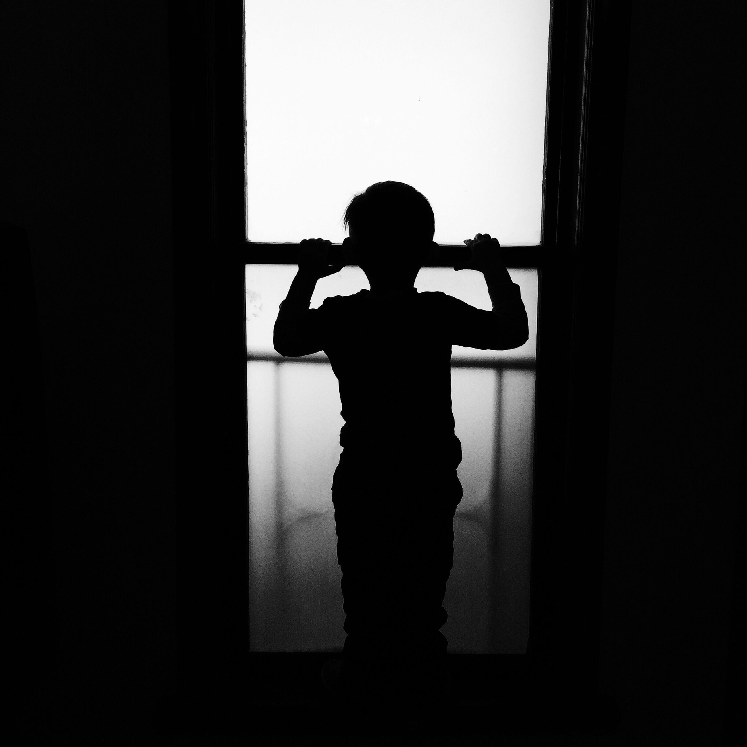 silhouette, indoors, lifestyles, full length, leisure activity, men, standing, copy space, window, dark, side view, three quarter length, rear view, togetherness, outline, person, home interior