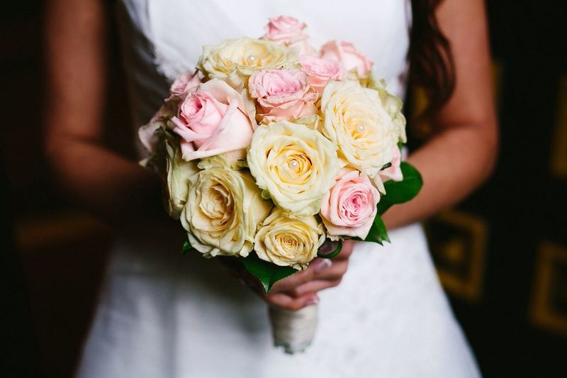 Mid section of a bride holding bouquet