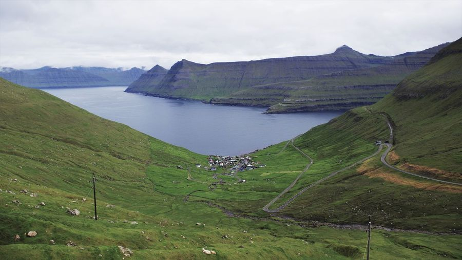 Funningur on the faroe islands within its beautiful v-shaped valley. Agriculture Beauty Cloud - Sky Clouds Cloudy Day Faroe Islands Fjord Fog Freshness Funningur Landscape Landscapes Mountain Nature No People Outdoors Rural Scene Scenics Sea Social Issues Valley Village Water Winding Road