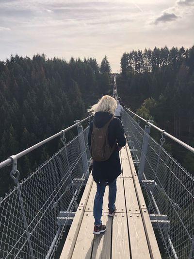 Wandern Morning Hike Hiking High Angle View Real People Tree Sky Railing Nature Full Length Leisure Activity Rear View Men Transportation Lifestyles Plant Hat People Footbridge Cloud - Sky Connection Day Women Bridge