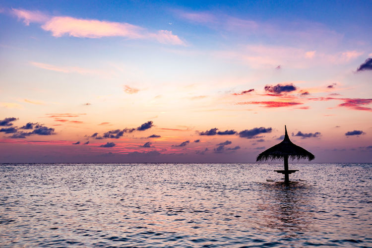 Thatched roof in sea against sky during sunset