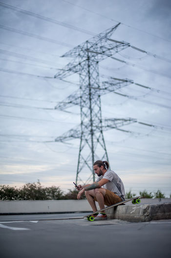Man sitting on mobile phone against sky