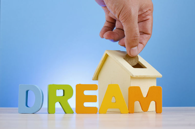 Mortgage and dream house concept,hand putting coins into house piggy bank over blue background. Human Hand Hand Human Body Part One Person Toy Text Toy Block Holding Real People Capital Letter Indoors  Finger Wood - Material Human Finger Leisure Activity Multi Colored Childhood Body Part Close-up Blue Background