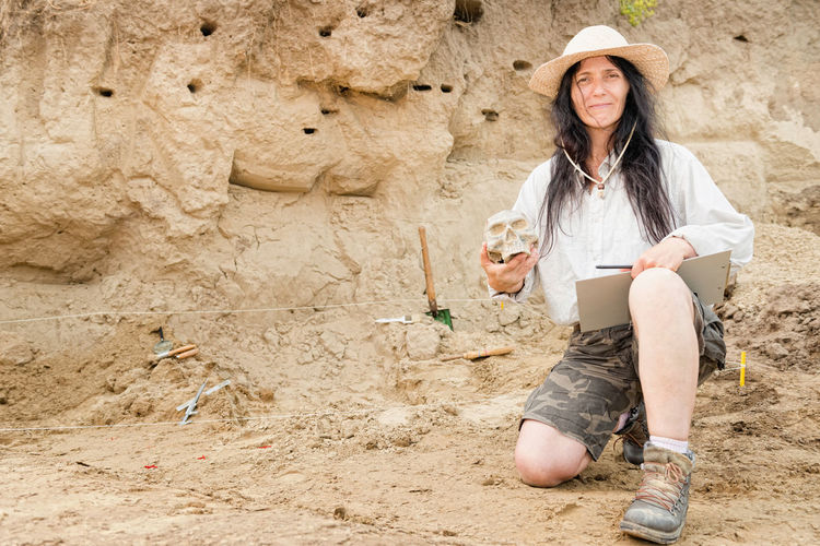 Archaeologist proudly presenting discovery at archaeological site