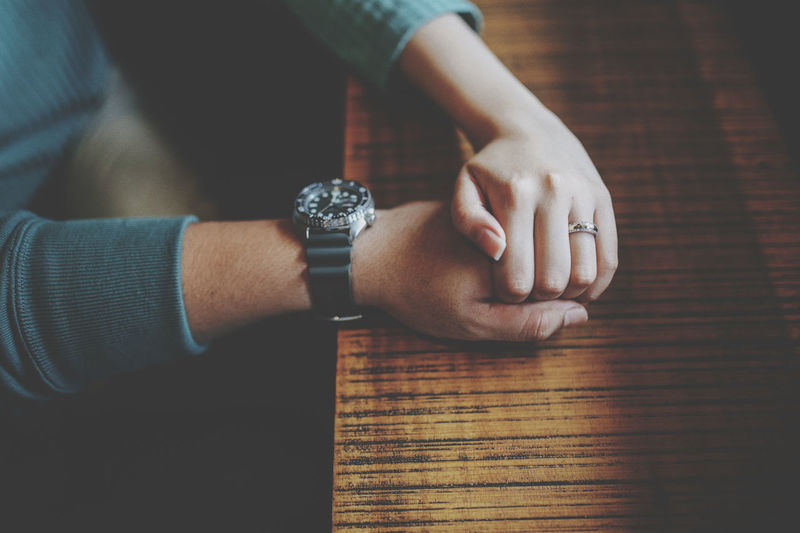 High angle view of couple holding hands on table