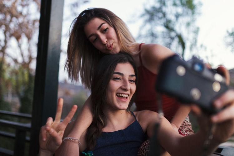 Lesbian couple taking selfie in balcony