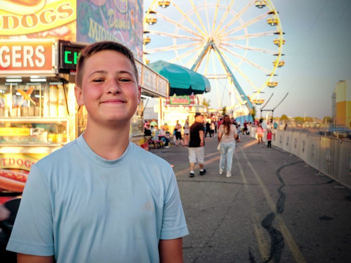 Nebraska State Fair - Grand Island, Nebraska August 2016 - This kid asked me to take a photograph of him as he walked past, who am I to say no. Americans Camera Work Carnival Rides Color Photography Cultures Daytime Elementary Age Eye For Photography EyeEm Best Edits EyeEm Gallery Fairgrounds Front View Fujifilm Getty Images Lifestyles Looking At Camera Nebraska Outdoors Photo Essay Portrait Selects Smiling State Fair Streetphotography Summertime