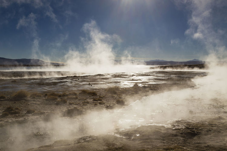 Smoke Emitting From Hot Spring Against Blue Sky