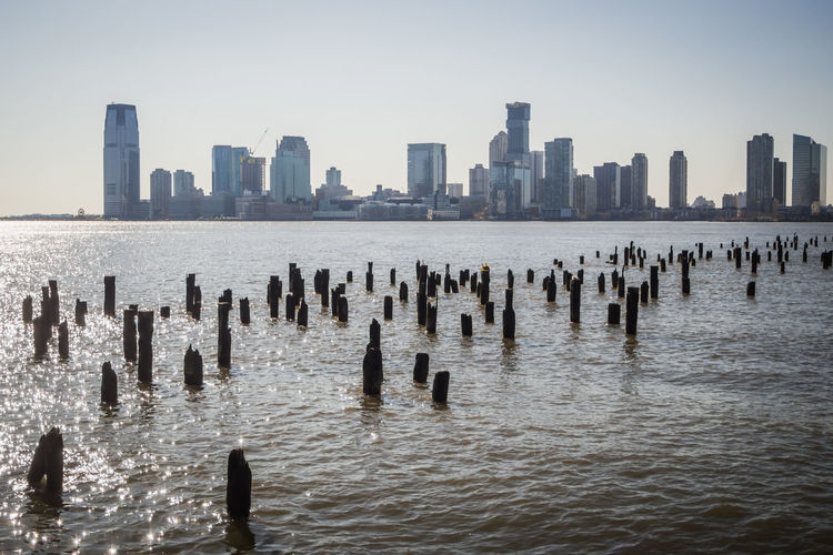 Wooden posts in sea against modern buildings in new york city
