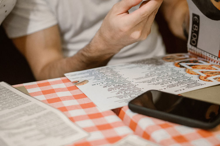 Menu Midsection One Person Indoors  Table Real People Paper Men Lifestyles Holding Communication Human Hand Selective Focus Text Leisure Activity Hand Publication Casual Clothing Sitting Book Finger Menu At The Restaurant Mobile Phone