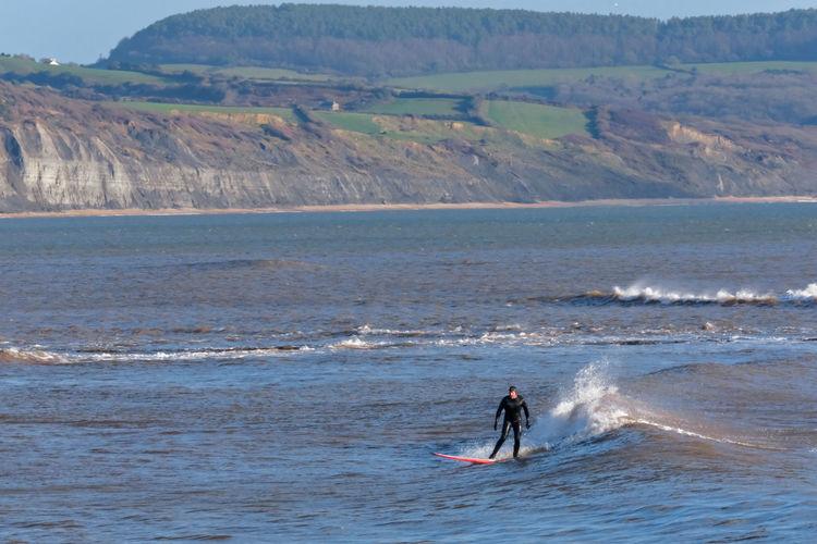 Man surfing on sea against mountain