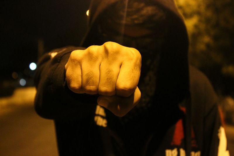 Close-up of man clenching fist wearing hood at night