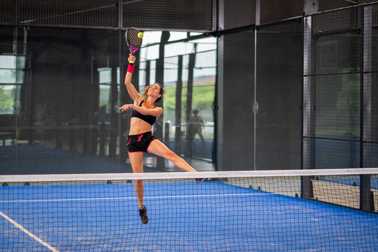 Woman playing padel in a blue grass padel court indoor - sporty woman padel player hitting ball