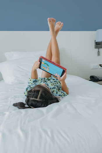 Midsection of woman resting on bed at home