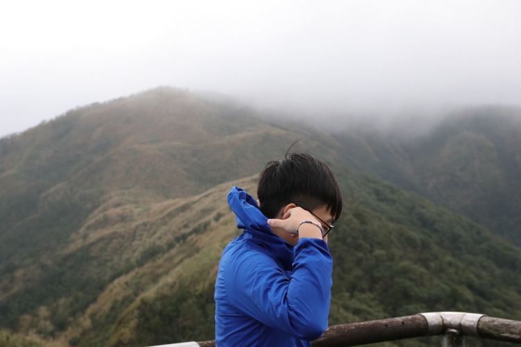 Side view of man wearing warm clothing against mountains during foggy weather