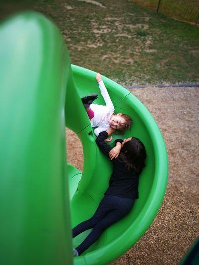 High Angle View Of Playful Sisters On Slide