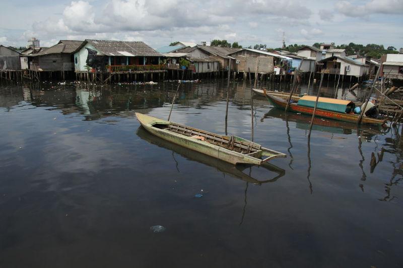 Boats moored in lake by buildings against sky