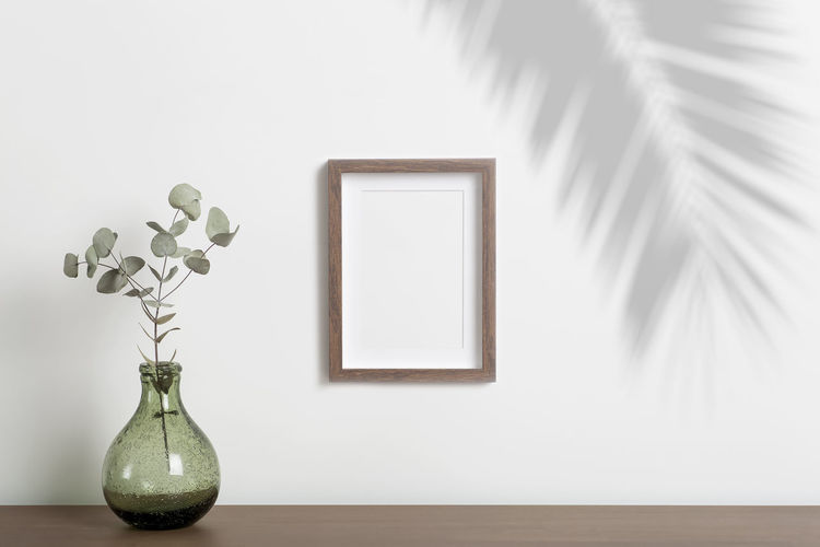 White flower vase on table against wall at home