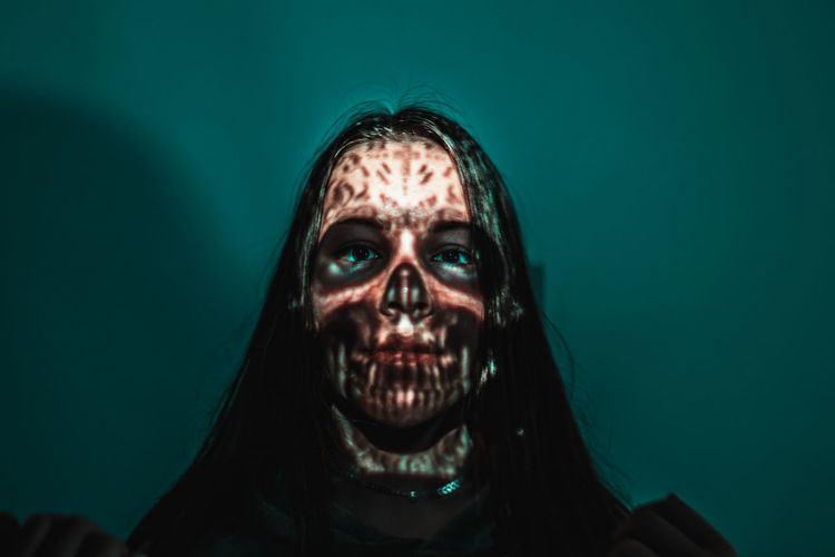 Close-up of spooky woman against blue background