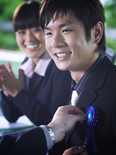 Cropped hand of businessman attaching badge on colleague