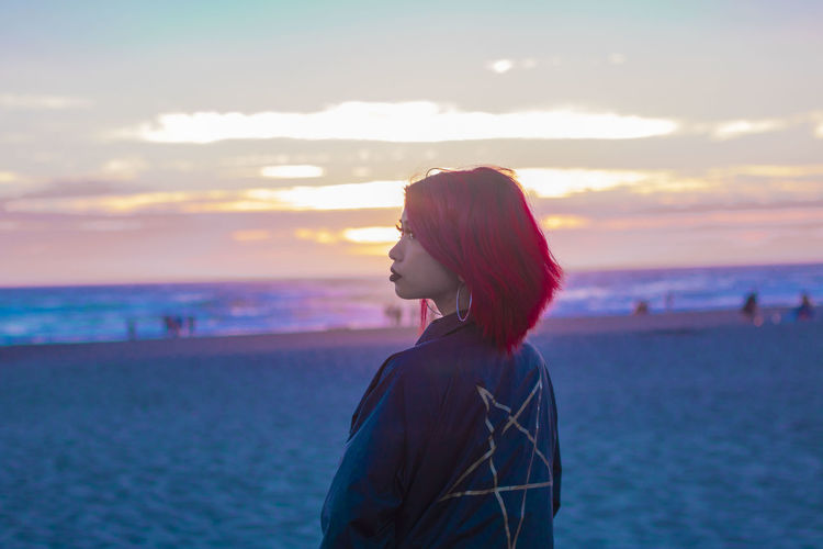 Rear view of woman with dyed hair while standing at beach against sky during sunset