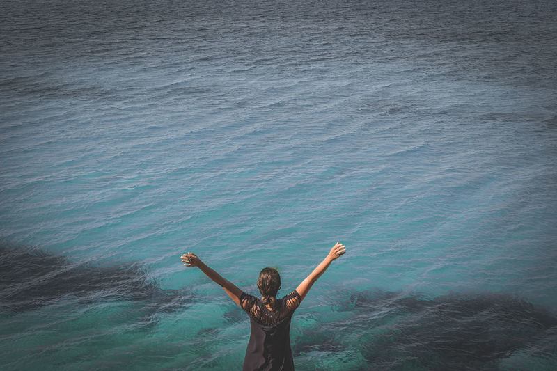 Man with arms raised standing in sea