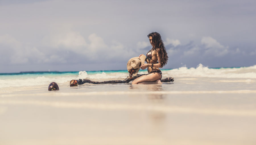 Side View Of Sensuous Woman In Bikini Kneeling At Sandy Beach