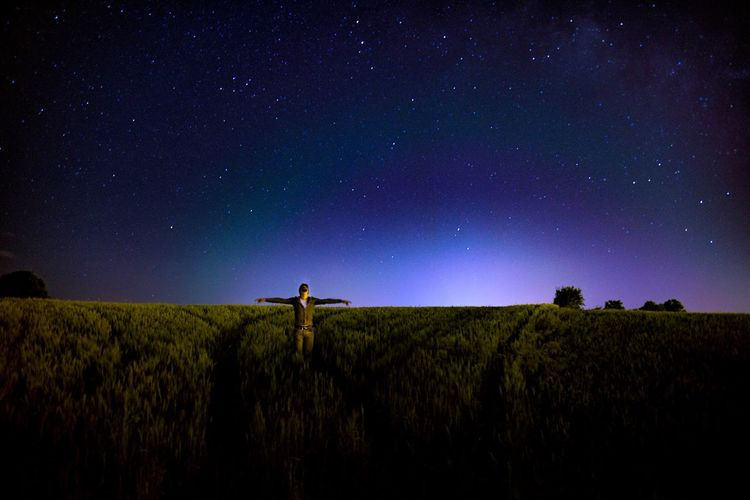 Man with arms outstretched standing on field against sky at night