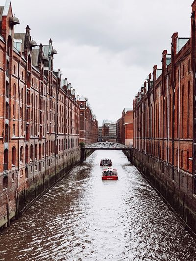 Canal amidst buildings in city against sky