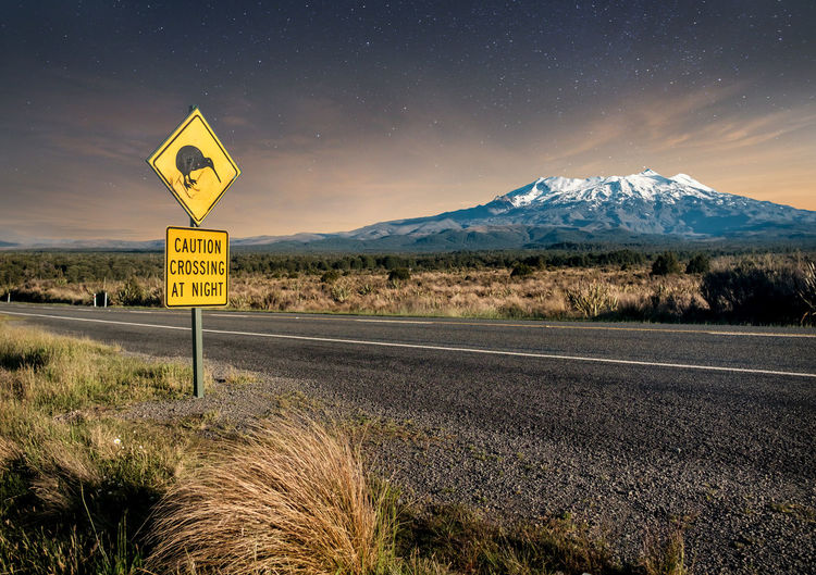 Kiwi road sign with snow covered mount ruapehu against starry sky