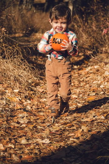 Portrait Of Boy Holding Pumpkin While Walking On Field