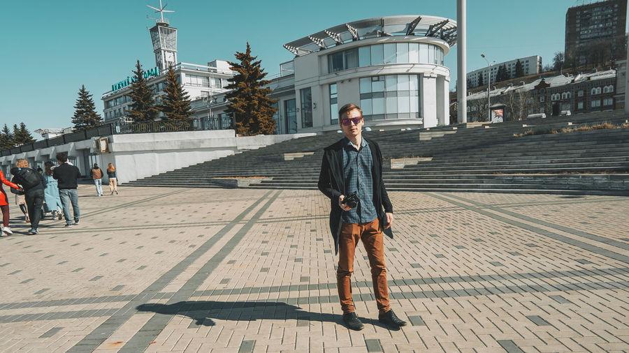 Man standing on footpath against buildings in city